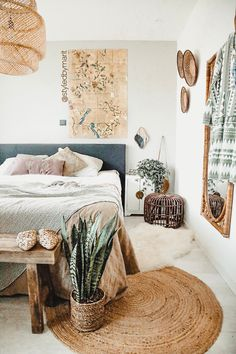 this white cool space is softened by the floor rug, layers of texture, soft linen and wall hanging