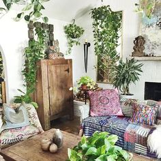 Boho woonkamer met batik kussens en urban jungle planten.