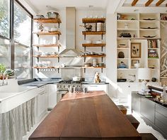 All in one kitchen, dining room, guest bedroom and small bathroom with vintage farmhouse sink with a striped skirt, open shelving reclaimed from a mill, floor to ceiling double hung windows and a wood block kitchen island