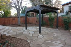 Rustic shade structure with lodgepole pine cover in flagstone patio