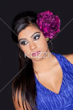 indian female fashion model with a flower in her hair posing. - Indian female fashion model with a flower in her hair posing white standing against black background, Model: Sabrina Remkissoon