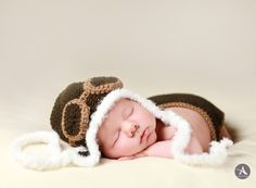 Newborn Keegan baby themed photo shoot. One week old, newborn photography in the Metro Detroit area by photographer Amanda Abraham Photography, Inc. Using props to enhance your newborn photo shoot. Aviator theme crochet outfit in studio.
