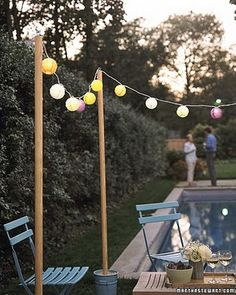 Garden-Glow Lanterns Don't have a place to hang lights? Wooden poles anchored in flower buckets filled with garden gravel can be set up anywhere there's level ground, and they help define an outdoor gathering place. Outdoor Movie Party, Outdoor Parties, Outdoor Entertaining, Outdoor Fun, Pool Parties, Dance Floor Lighting, Patio Lighting, Lighting Ideas, Cafe Lighting