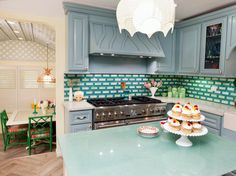 To suit her clients' love of eclectic interiors and all things vintage, designer Meg Caswell created this kitchen that has a decidedly whimsical, retro vibe. Fused glass tiles in shades of blue, green and white create a funky backspash while the wall cabinets receive a coat of soft powder blue paint. Meg tops the island with a glass countertop with just a hint of green, reminiscent of the jadeite pieces collected by the homeowners.