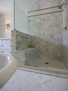 Calacatta marble enrobes this glass-enclosed shower, to showstopping effect. The built-in seat has a dual function: Not only does it provide a perch for grooming or relaxing, but it also shields bathers from the sink area.