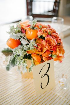 Fall wedding? orange arrangement of persimmon, orchids and roses by Charleston Stems