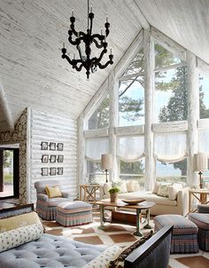 Views of the lake are framed by soaring windows in this whitewashed log cabin. By Jessica Jubelirer Design.