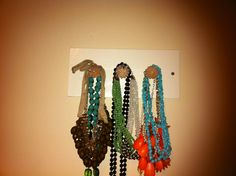 This is a simple board with doorknobs drilled into it. A DIY necklace display to organize Chelsea's jewelry in her normally cluttered dorm room.