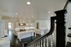 A black and white staircase leads to an open floor plan kitchen featuring three industrial pendants illuminating a white center island with legs topped with white marble facing a kitchen peninsula overlooking the living room.