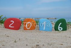 Happy 2016 on colourful stones with beach background