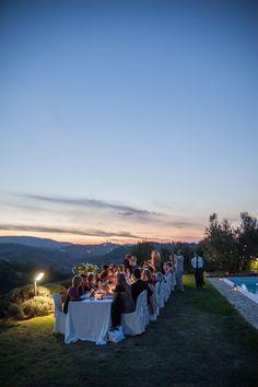 Abendessen an einer langen Tafel mit Blick auf San Gimignano Aus unserem Fotoalbum: Protestantische Hochzeit in der Toskana auf einem Weingut Bei dem Abendessen mit allen Gästen an einer langen Tafel genießen alle die atemberaubende Aussicht auf das abendliche San Gimignano.