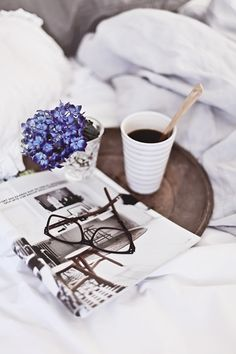 Lounging in Bed on a Sunday morning with something to read, fresh flowers, and  coffee.