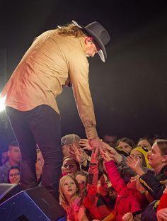 Country music singer Trace Adkins takes time out his USO show at Misawa Air Base to reach down and shake hands with airmen and their families on November 28, 2012. This is Adkins seventh USO tour since 2002.