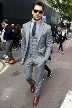 Opt for a grey three piece suit and a white and black vertical striped oxford shirt to ooze class and sophistication. Want to go easy on the shoe front? Opt for a pair of dark brown leather double monks for the day.   Shop this look on Lookastic: https://lookastic.com/men/looks/three-piece-suit-dress-shirt-double-monks/14362   — Dark Brown Sunglasses  — White and Black Vertical Striped Dress Shirt  — Charcoal Tie  — Grey Three Piece Suit  — Dark Brown Leather Double Monks