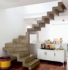 """Cimento queimado - A escada em """"U"""", tipo cascata, com degraus em concreto maciço, dá leveza ao ambiente. Feita em concreto armado e revestida com cimento queimado"""