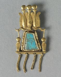 An ancient Egyptian pendant in the form of an multiple-atef crown, with an eye of Horus, symbol of wellbeing and wholeness, at the centre.