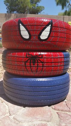 Tire Spider Man Superhero character made from old car tires and Glidden exterior paint. Repurposed super hero project for school. Recycled tire art. Garden planter idea. DIY. Image only.