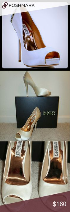 "Badgley Mischka Ivory Satin Kiara Pump Stunning ivory satin peep-toe stilettos in like new condition. Heel, 5""; platform, .75"". Bought for my wedding, but ended up only using for photos (I needed 6"" heels). Worn briefly on carpet in bridal suite. Rubber tips in unworn condition. Minor imperfections on one heel as circled in photo (they came that way) & can't be seen in my wedding shots. Replacement jewels & tips included. Will ship in box. If I can find the dustbag it's yours (may be in…"