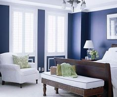 Indigo blue walls (and other deep colors like gray or navy) look good paired with neutral furnishings. Like the sleigh bed, the wicker bench to catch the comforter, the slip-covered chair, plantation shutters, even the use of trim to create a wainscot detail on the wall. Nice old light fixture.