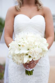 White bridal bouquet of calla lilies, orchids, hydrangea, and roses.
