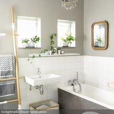 Die Badezimmergestaltung in Grau und Weiß wirkt durch vereinzelte, helle Holzelemente natürlich und ungezwungen. Auch durch kleine grüne Pflanzen und Korb- sowie…