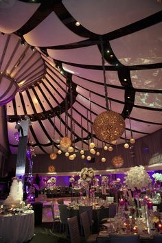Guests were seated beneath a dramatic ceiling decorated with spherical light fixtures inside the Ahmanson Ballroom at the Skirball Cultural Center. #LightingIdeas Photography: Dalal Photography. Read More: http://www.insideweddings.com/weddings/glam-modern-wedding-with-purple-decor-in-los-angeles-california/342/