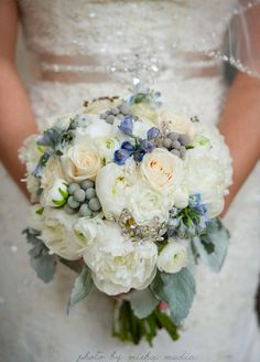 white peonies, cream Vendela roses, white ranunculus, silver sage foliage, silver brunia, hybrid light blue delphinium and crystal brooches