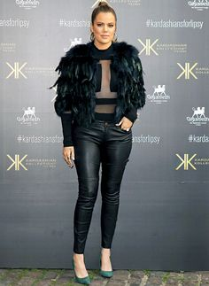 Khloe Kardashian in a sheer top, leather pants, and feather jacket.