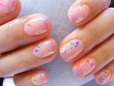 Light pastel pink nails with multi colored glitter and chunky colored pieces.