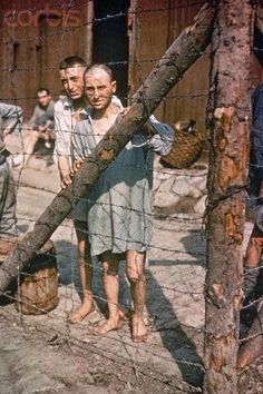 Two World War II prisoners of war stare through a barbed wire fence at Buchenwald Concentration Camp near Weimar, Germany in 1945. Pin by Paolo Marzioli