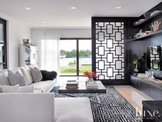 Another Kyle Bunting rug exhibits a classic Greek key pattern in the media room, a subtle homage to Cynthia's heritage. A graphic divider made by Thomas Riley Artisans' Guild nods to the rug motif. A white linen Minotti sofa balances the room's richness.