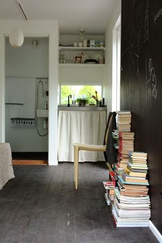 kitchen with book stacks and chalkboard wall.