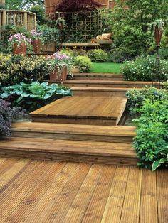 Shallow wooden steps provide a space for decorative pots, and a wood bridge leads over a small pond to a grassy sitting area.