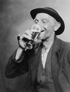 Happy old man drinking glass of beer, with his daintier finger extended. 1937.