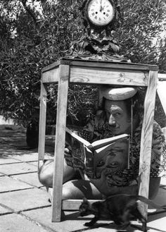 Surrealist artist Salvador Dali in a bizarre pose sheltering from the sun in the garden at his home in Cadaques on the Spanish Costa Brava. The book he holds, needless to say, is upside down. January (Photo by Charles Hewitt) Black And White Portraits, Black And White Photography, Famous Artists, Great Artists, Home Beach, People Reading, Salvador Dali Art, Les Religions, Charles Darwin