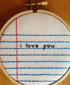 This is a 4 wooden hoop with the words i love you stitched on platinum colored aida fabric with a notebook paper design. Can be hung on a wall or placed on a shelf. /// MADE TO ORDER: Will take up to 3 days to create. More