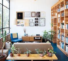 Perfect combo of bright, sunlit space, built-in bookshelves, live plants, salon-style wall art, and mix of modern and vintage furniture.