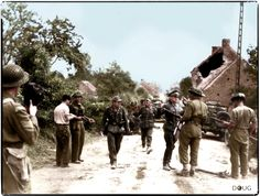 Major David V. Currie, VC (left with pistol) of the 29th Canadian Armoured Reconnaissance Regt. (SAR), is in conversation with R. Lowe of 'C' Company, at the time that members of 2.Pz.Div., commanded by Hauptmann Siegfried Rauch are surrendering to Sgt.Major G. Mitchell in Saint-Lambert-sur-Dives, Calvados. (The Falaise Pocket) on the 19 August 1944. Major Currie received the V.C for his courage and leadership.