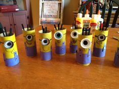 DIY Easy Minion Craft!   Super cheap and very easy! -toilet paper rolls  -yellow paint -blue construction paper (overalls) -metal or plastic bottle caps (goggles) -black foam (eyes and hair) -hot glue for goggles and hair -regular or stick glue for overalls and straps -black marker to draw on mouths, goggle straps and buttons Ready. Set. Build Minion Army!!!