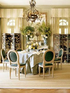 a dining room with a skirted round table and decorative screens