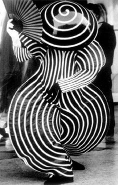 "Oskar Schlemmer's ""Das Triadische Ballet,"" Stuttgart, Germany 1922. Based on spirals and circles, this costume is mesmerising. It features a hat shaped like an upside-down bowl with a spiral on it, a full body costume shaped to curve out from the body. It is black and white in this particular photograph, adding to the effectiveness of the piece."