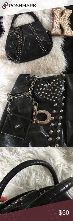 "Bebe Studded Charcoal Black Purse with charm Outside is in excellent condition. No rips or tears to leather, handles show no signs of wear, charm show no major scratches. Last picture does show a small flaw on the backside of purse very small , and inside lining has a small tear shown in second to last picture. Inside has no major wear or staining , just a little dust that will be cleaned off before shipping. Width: 14.5"" Length: 12"" Drop: 6.75"" bebe Bags"