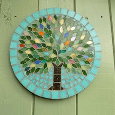 The Design This mosaic tree has a slightly tapestry feel to it, with random leaves made with bright, translucent, iridescent, and metallic streaked tiles adding jewel like shine and sparkle against the other green leaves. The background and border is a light jade green, and the tree has the deep colours of foliage and flowers in Summer. Each Jewel Tree is designed to compliment any of the other season trees so you can have any combination of seasons that means something to you, or that you…