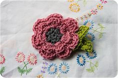 instructions are for crochet flower - but i like the embroidered flowers on background fabric, with lots of detached-chain petals