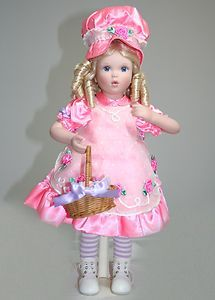"""Cupcake"" Collector Doll (Danbury Mint)  by Elke Hutchens  Cupcake is a fabulous porcelain doll wearing a sweet pink dress with darling flower accents.  She has beautiful blue eyes and cute blonde hair done in curls!    She's comes with a yummy basket of goodies (cupcakes) and has a matching mushroom poke bonnet.    She is 19 inches tall, in mint condition, and new in the box, comes with certificate of authenticity.    Cupcake is Ready to come home for the Holidays!"