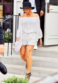 Beyoncé wears an off-the-shoulder top, lace eyelet shorts, strappy heels, and a black fedora