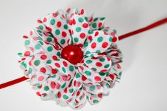 This is a SUPER CUTE red and green polka dot flower headband. It also has a red centerpiece! It would go with many different outfits and is
