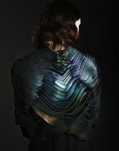 """Evolutive Organic Materials by Unseen  """"Lauren Bowker a fondé le studio The Unseen, spécialisé dans la recherche expérimentale de matériaux textiles. Pour ce projet nommé Air, le studio s'est axé sur l'iridescence naturelle et a apprivoisé ses incroyables palettes de couleurs changeantes en l'appliquant à une sculpture organique portée par un mannequin."""""""