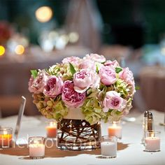 Mixed among taller centerpieces, Brittany ordered smaller ones that mimicked her bouquet with the same antique hydrangea, David Austin roses, and curly willows.