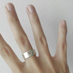 Anillo, ajustable en plata ley 999, de 5 cm de largo, por  0.65 cm de alto, es una banda con un pequeño corazón calado en el centro. 100% hecho a mano.